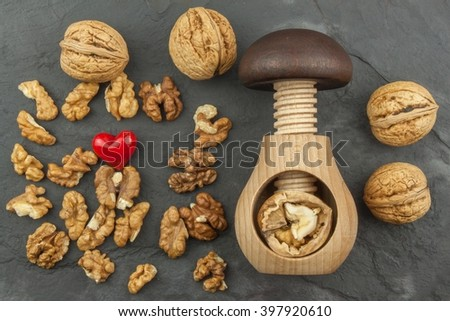 Walnut kernels and whole walnuts on slate.  Walnuts and wooden nutcracker. We like walnuts. Advertising on walnuts. - stock photo
