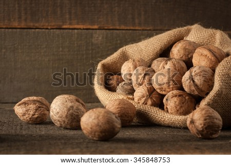 Walnut kernels in sack and whole walnuts on rustic old wood.