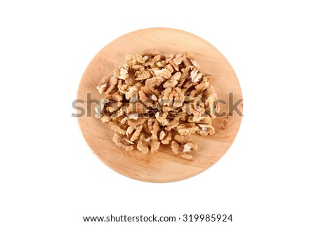 Walnut kernels on a wooden plate isolated on white background - stock photo