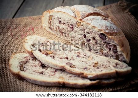 Walnut loaf artisan bread sliced open on wooden board  - stock photo