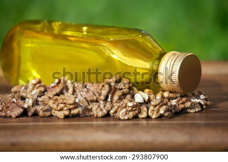 Walnut oil in bottle and nuts on a wooden table. - stock photo
