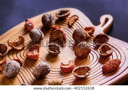Walnuts and dried fruits on a wooden board in apple form - stock photo