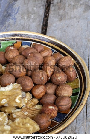 Walnuts and hazelnuts in an old bowl in a rustic farmhouse. - stock photo