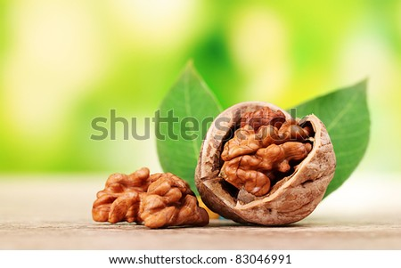 walnuts and leaves on wooden table on green background