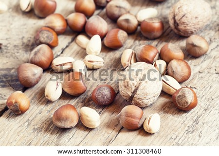 Walnuts, hazelnuts and pistachios on a wooden table, toned image, selective focus - stock photo