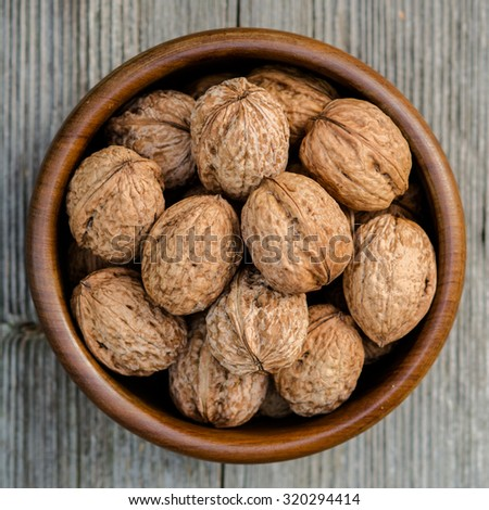 walnuts in a bowl - rustic wooden table, top view - stock photo