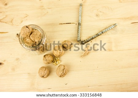 Walnuts in a Glass and a Nutcracker on a Wooden Table