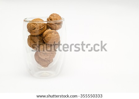 Walnuts in a glass isolated against white background