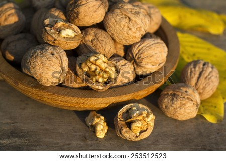 Walnuts in a wooden plate on rustic old table