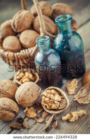 Walnuts in basket and nuts tincture or oil on old wooden table - stock photo