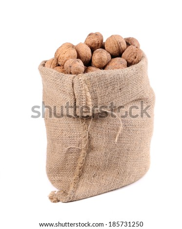 Walnuts in burlap bag. Isolated on a white background.