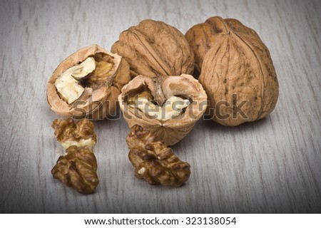 walnuts in shell and open on wood gray table   - stock photo