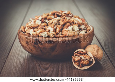 walnuts in the brown wooden bowl on table - stock photo