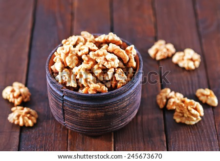 walnuts in wooden bowl and on a table - stock photo