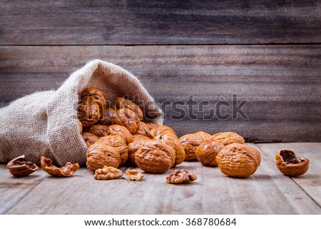 Walnuts kernels in hemp sack and whole walnuts on rustic old wooden background. - stock photo