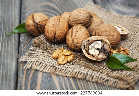 walnuts on a burlap sack  on old wood table - stock photo