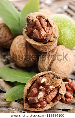 walnuts with green leaves, on  wicker background - stock photo