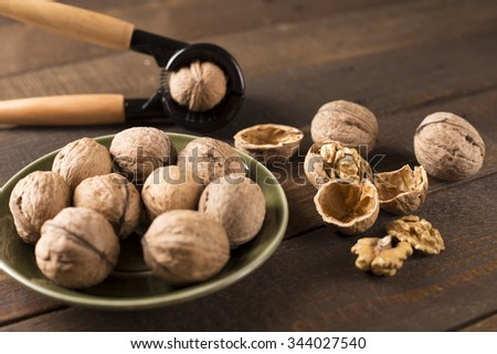 walnuts with nutcracker on a green plate