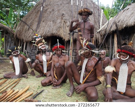 Wamena, Indonesia - January 23, 2015: Dani tribe men sitting in front of their huts dressed with ritual costumes