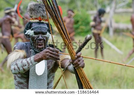 WAMENA, PAPUA, INDONESIA - November, 14: Yali Mabel, the chief of Dani tribe performing traditional fighting dance on November, 14, 2008 near Wamena, Papua, Indonesia. - stock photo
