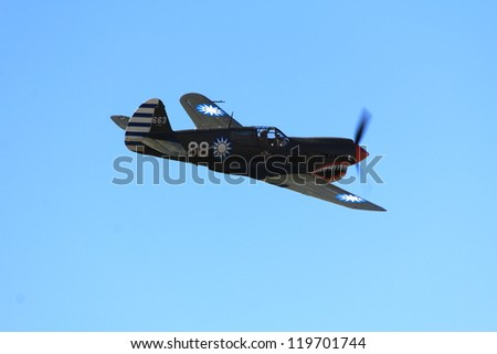 """WANAKA MARCH 03: Curtiss P-40 Kittyhawk Spitfire aircraft flies during the royal New Zealand air force 75th anniversary""""Warbirds Over Wanaka"""" airshow on March 03, 2012 in Wanaka New Zealand - stock photo"""