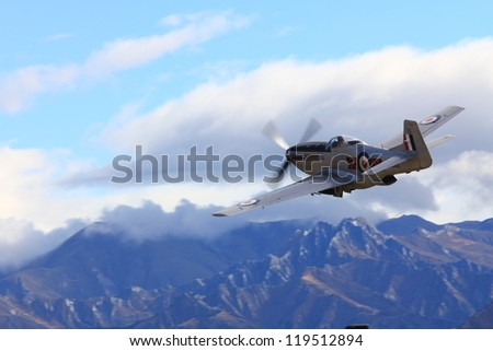 """WANAKA-MARCH 03: P-51D Mustang aircraft flies over the mountains during the royal New Zealand air force 75th anniversary """"Warbirds Over Wanaka"""" airshow on March 03, 2012 in Wanaka New Zealand - stock photo"""
