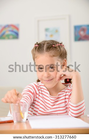 Want to be a  real painter. Nice little positive girl putting the brush in glass with water and sitting at the table while enjoying painting. - stock photo