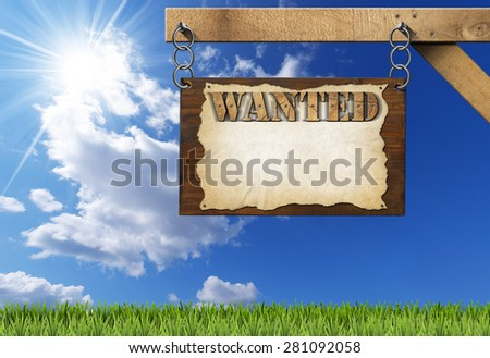 Wanted - Wooden Sign with Chain. Dark wooden sign with torn empty parchment with text Wanted. Hanging from a metal chain on a wooden pole on blue sky with clouds and sun rays - stock photo