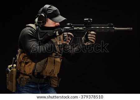 war, army, weapon, technology and people concept - young soldier or private military contractor holding sniper rifle and aiming. Image on a black background. - stock photo