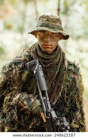 war, hiking, army and people concept - young sniper or ranger with sniper rifle in forest