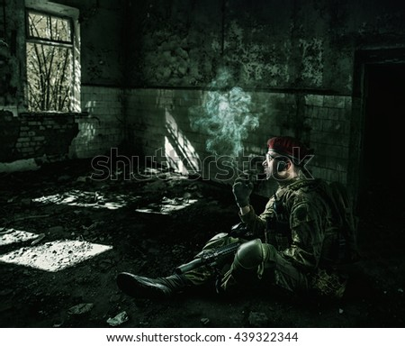 war. weary soldier wearing military uniform with automatic riffle  sitting at night in the destroyed building - stock photo