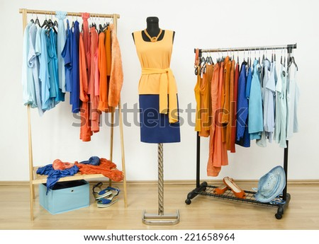 Wardrobe with complementary colors orange and blue clothes arranged on hangers. Dressing closet with clothes, shoes and accessories and an outfit on a mannequin. - stock photo