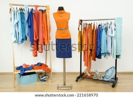 Wardrobe with complementary colors orange and blue clothes arranged on hangers. Dressing closet with clothes, shoes and accessories and a autumn outfit on a mannequin. - stock photo