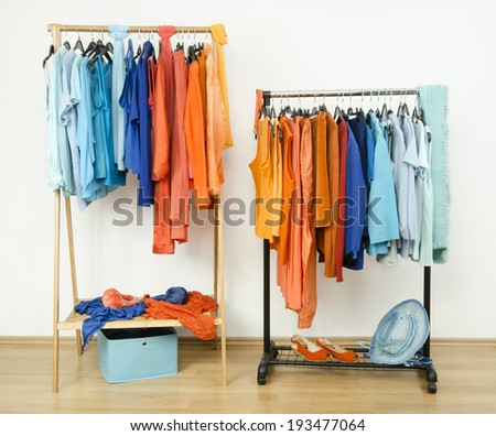 Wardrobe with complementary colors orange and blue clothes hanging on a rack nicely arranged. Color coordinated clothes on hangers and accessories in a store.