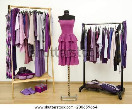 Wardrobe with purple clothes arranged on hangers and a dress on a mannequin. Dressing closet with all shades of violet clothes, shoes and accessories. - stock photo