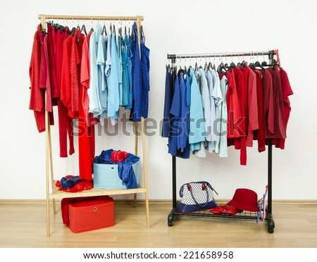 Wardrobe with red and blue clothes hanging on a rack nicely arranged. Color coordinated clothes on hangers in a dressing room. - stock photo