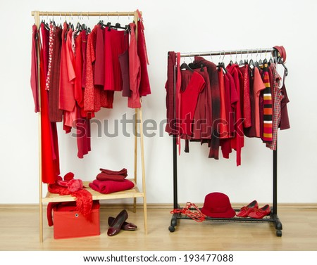 Wardrobe with red clothes hanging on a rack nicely arranged. Red clothes on hangers and accessories in a dressing room. - stock photo