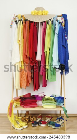 Wardrobe with summer clothes nicely arranged by colors. Dressing closet with color coordinated clothes on hangers, sandals and accessories. - stock photo