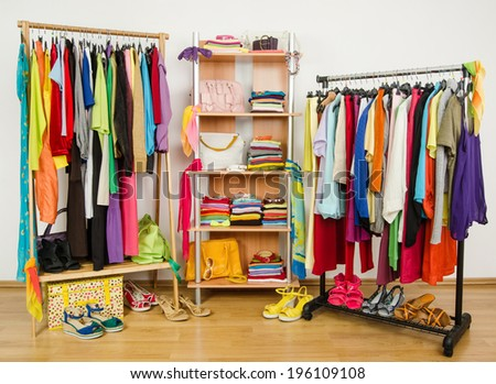 Wardrobe with summer clothes nicely arranged. Dressing closet with colorful clothes and accessories on hangers and a shelf. - stock photo