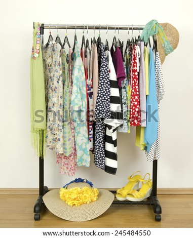 Wardrobe with summer clothes nicely arranged. Dressing closet with colorful clothes on hangers,sandals, hats and accessories. - stock photo