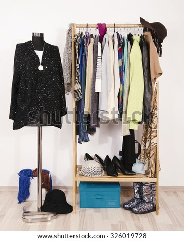 Wardrobe with winter clothes arranged on hangers and a festive sparkly outfit on a mannequin.Dressing closet with autumn clothes and accessories.Tailor's dummy wearing sequins sweater and black skirt. - stock photo