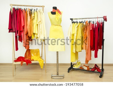 Wardrobe with yellow, orange and red clothes arranged on hangers and a yellow outfit on a mannequin. Dressing closet with bright color coordinated clothes on hangers, shoes and accessories.