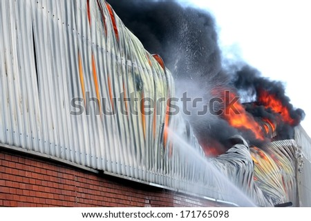 Warehouse building burning with intense flames  - stock photo
