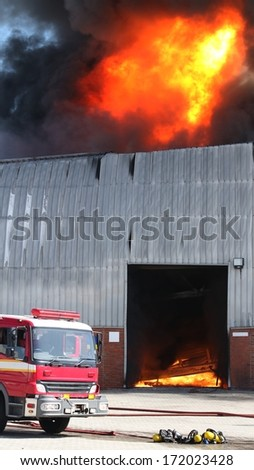 Warehouse building burning with intense flames and fire engine attending - stock photo