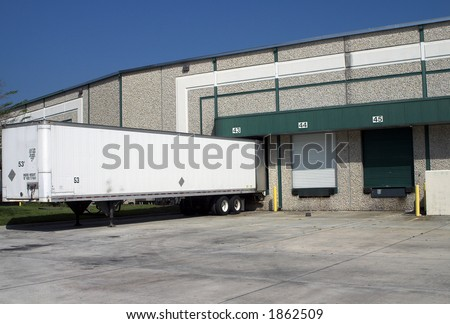Warehouse building loading bays with empty trailer - stock photo