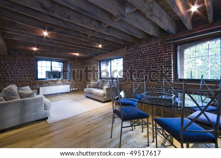 Warehouse conversion contemporary living area with large sofas and dining table for seven - stock photo