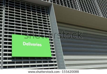 warehouse entrance with green deliveries sign - stock photo