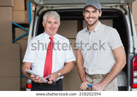 Warehouse manager and delivery driver smiling at camera in a large warehouse - stock photo