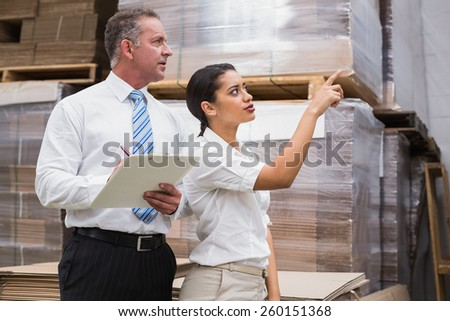 Warehouse manager and her boss checking inventory in a large warehouse - stock photo
