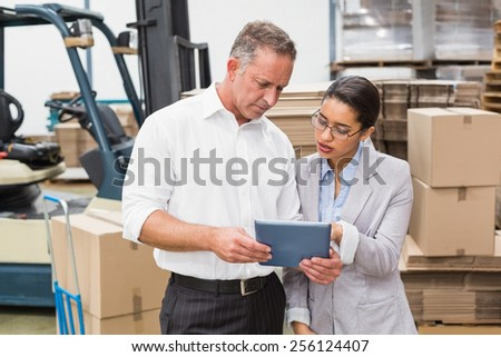 Warehouse manager and her boss working together in a large warehouse
